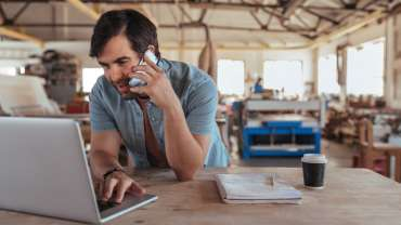 A sole trader in a phone call inside his workshop.