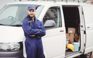 A carpenter holding a hammer standing outside his van.